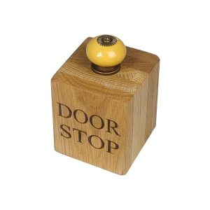 Small solid oak doorstop with yellow door knob