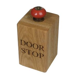 large solid oak doorstop with red door knob