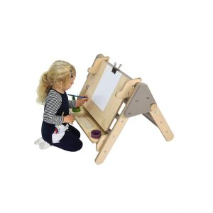 Thea kneeling at Nursery Pikler Desk easel